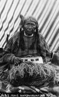 Mary a Yakima Indian, age 120 yrs., is sitting on blankets holding a weaving and has a hair ornament on one of her braids.  Date:  between 1880 and 1910?                                ...