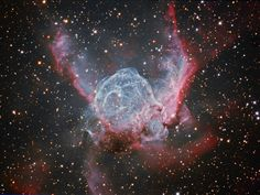 The Thor's Helmet Nebula is an emission nebula in the constellation Canis Major. The nebula is approximately 15,000 light-years away and 30 light years in size. Known as a Wolf-Rayet star, the central star is an extremely hot giant thought to be in a brief, pre-supernova stage of evolution. It is similar in nature to the Bubble Nebula, interactions with a nearby large molecular cloud are thought to have contributed to the more complex shape and curved bow-shock structure of Thor's Helmet.