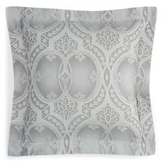 Reminiscent of an ornate iron gate, a detailed woven pattern in grey and pearl adorns this regal sham by Frette.