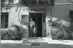 """Robert McCabe, the Belle Hélène Hotel, Mycenae, 1955 - Agamemnon and his daughter Panagoula. The sign above the door reads: """"Hail Stranger. You are welcomed by us here."""" According to McCabe generations of archaeologists stayed at this small hotel which is owned by a family whose names are all taken from Homer."""