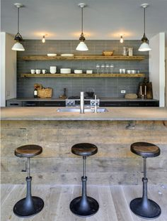 12 Kitchen Counters: This is the Hamptons home of blogger Athena Calderone of design firm Rawlins Calderone Design. While she designed the interiors, she and her DJ husband hired Bates Masi to rework the architecture. The newly constructed interior walls and interior cabinetry, including the island, are done in reclaimed barn wood, which blends perfectly with the industrial-style stools.