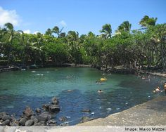 don't miss this if you are on the big island----------- ahalanui park is also known as pualaa county park. It is located about 30 miles south of hilo. It is right on the ocean but separated from the ocean waves by a low wall made from lava rock. The cooling waves do wash over the wall, which is what keeps the water, fed by natural springs that are thermally heated by the volcano, at a balmy temperature of about 90 degrees.
