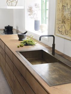 Brass insert around sink on wooden counter -- good idea! Bordpladen er som resten af køkkenet lavet af en lang planke. Vasken i håndsmedet messing fremstiller Garde Hvalsøe selv. Blandingsbatteri fra Quooker.