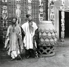 Africa | The son's of the Sultan (King Njoya) standing next to a Drum at the entrance of the Palace, Cameroon.  ca. 1911 - 1915 | ©Anna Wuhrmann