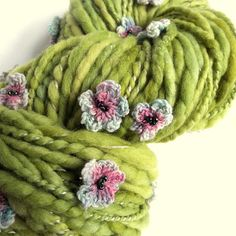 Flower art yarn. Green handspun knitting yarn. Art yarn spun using gorgeously soft blue faced leicester fibre, plyed with pale green lambswool and silk thread. Beautiful soft lettuce green colour. This art yarn is created with pink and blue crochet flowers scattered throughout (28). The flowers are all handmade and have beaded centres. This wool is totally unique and will make any project a real show stopper. It will also knit up really quickly and give your creation great texture! Hand dyed…