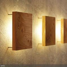 Schlichte und moderne Wandleuchte mit hinterleuchteter Platte aus Massivholz.