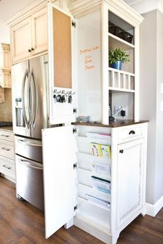 The end cabinets in a kitchen layout typically get fitted with a door facing for a polished look. Here the homeowner has found a clever space for keys, a pegboard and a dry erase board for notes and to-do lists, and installed slats for magazines and cookbooks.