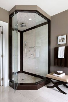 This spacious walk-in corner shower is encased in rich dark wood and light tile. The shower features a hand-held shower head along with a rainfall shower head.