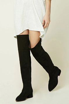 A pair of faux suede knee-high boots featuring a side zipper, pointed toe, and a block heel.