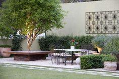 Espaço de convivência ao ar livre com jabuticabeira e um banco 360°, mesa com…