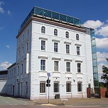 A four-storey brick building with glass rooftop extension