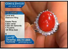 Large coral cabochon sits in a bed of diamonds in this ring made in 18k gold.