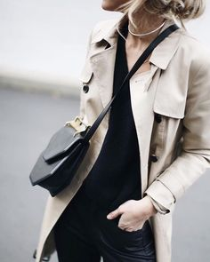 her paperweight- all black, classic trench, silver necklace, black bag with gold accents. Fall fashion and street style.