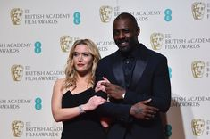 Award presenters British actors Kate Winslet (L) and Idris Elba (R) pose together in the winners area at the BAFTA British Academy Film Awards at the Royal Opera House in London on February 14, 2016.