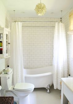 claw-foot tub; floor: white penny tile; wall: subway tile; ruffled curtains with a shower curtain liner; chandelier; wooden stool