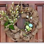 """Made this for Christmas! Easy burlap wreath using metal wreath form and burlap ribbon.  Used cutout glittery """"Joy"""" sign, red raffia & feather picks, & a battery flickering flame candle in a pine cone candle holder."""