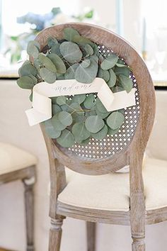 Cane-back sweetheart chair adorned with a eucalyptus wreath | Photo by Deborah Zoe