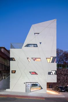 This towering Seoul residence created by South Korean architect Moon Hoon for a photographer and his mother, features a relief-patterned facade punctured by small windows.