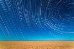 Mar de Ajo, Buenos Aires Province, Argentina. | Multiple shots are compiled to create a time-lapse effect, as the Earth's rotation draws the light from the stars into long trails arcing over the beach.