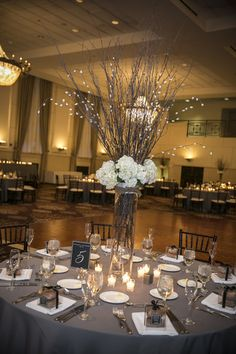 Tall, glamorous white flower centerpieces featured a tall glass vase with branches and white blooms {Green Holly Weddings}
