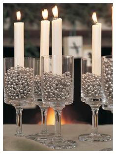 What would the holidays be without the warm, flickering glow of candlelight? Materials: * Drinking glasses * Silver garland of beads * Taper candles Instructions: * Fill each glass with silver beads and insert a candle taper. New Years Decorations, Christmas Decorations, Christmas Candles, Table Decorations, Gold Christmas, Birthday Decorations, Deco Nouvel An, New Year Table, Decoration Evenementielle