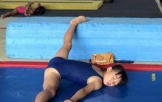 厳しい開脚柔軟トレーニングで目を閉じながら痛みに耐え続けるジュニア女子体操選手