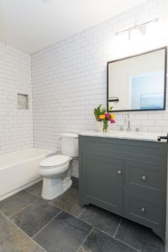 White subway tile with gray grout, slate quartzite floors, modern gray vanity with Carrara Marble vanity top.: