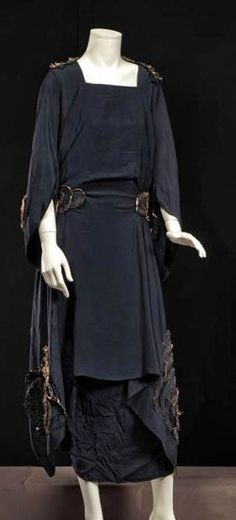 Afternoon dress, Maison Francis, Paris, ca. 1920. Dark navy crêpe de chine with stylized flowers cut from same fabric. Skirt with a draped apron effect, asymmetrical length. Long sleeves with medieval-style pointed ends. Cornette de Saint Cyr