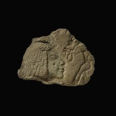 Fragment of limestone sunk-relief carving showing the head of Queen Nefertiti offering a papyrus-frond to the Aten. The Queen wears the short wig and uraeus. A trace of red pigment is visible.