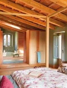 Dormitorio con cama de dosel y techo abuhadillado de madera. Dormitorio