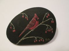 Cardinal hand painted on a rock by Ann Kelly.