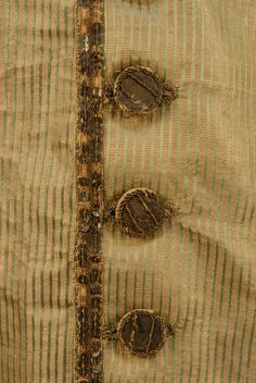Button detail, waistcoat, c. 1770. Raised green vertical striped silk over gold having a horizontal rib, trimmed with a double band of sequins and metallic gold thread, eleven original sequin trimmed buttons.