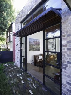 Recycled brick was used extensively inside and out, for both environmental and aesthetic reasons. Lightweight steel-framed windows and doors were painted black to emphasize the tall brick walls in the dining room and the courtyard.