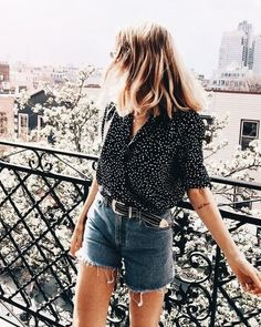 Polka dot blouse with denim shorts.