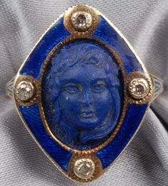 An Art Deco lapis and diamond cameo ring depicting a young lady with flowers in her hair, bezel-set with diamond melee, bezel, shoulders, and shank with champleve enamel accents