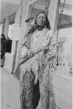 Man wearing peace medal posing with rifle outside of store, 1922? Sans Arc Sioux. Bureau of Catholic Indian Missions