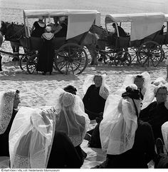 Huifkarren en vrouwen in Zeeuwse klederdracht op het strand tijdens feestelijkheden ter gelegenheid van de sluiting van het Veerse Gat (1962) Op de voorgrond vrouwen in de Thoolse dracht, bij de huifkarren zie je de Zeeuwse dracht