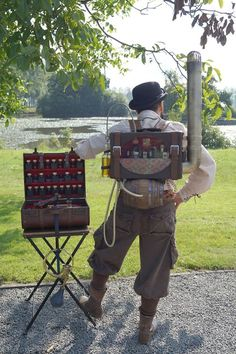 Steampunk Bartender and Backpack Bar (mobile bar with liquor and alcohol bottles and shot glasses) - For costume tutorials, clothing guide, fashion inspiration photo gallery, calendar of Steampunk events, & more, visit SteampunkFashionGuide.com