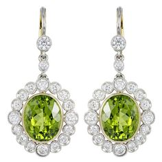 Peridot and Diamond Drop Earrings. Platinum and 18 karat yellow gold vintage style drop earrings consisting of 2 oval shaped peridot having a total weight of approximately 8.00 carats, the center stones are surrounded by 1 row of full cut diamonds having a total weight of 1.80 carats.