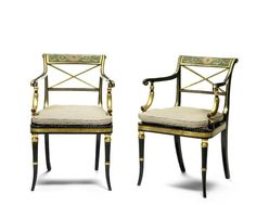 A pair of Regency ebonised, parcel gilt and decorated open armchairs. The rectangular scrolling panelled backs painted with scrolling leaves and central paterae on a green ground above 'X' shaped splats, shaped open arms and curved arm supports, on rectangular caned seats, on ring turned outswept legs.