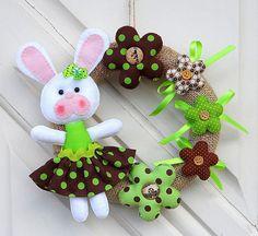 Guirlanda com coelho de páscoa, confeccionados em feltro. Flores em tecido e feltro. Pode ser feita em qualquer cor. Diâmetro da guirlanda: 21 cm