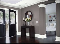 White trim and a light ceiling keep this entry bright despite the sleek dark wood floors and black doors and furniture. A slightly warm gray on the walls keeps it feeling homey and welcoming.