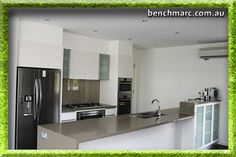 Modern kitchen with waterfall bench, glass cupboard doors and glass splashback