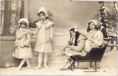 Vintage real photo postcard.  Four girls posed in a photographers studio with a sled.