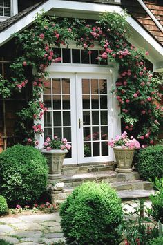 [I like the way the climbing roses and light pink geraniums (pelargoniums) set off the French doors and transom.  The stone steps add to the romantic look.