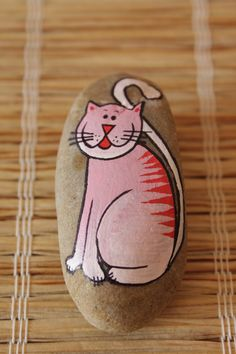 Cute pink cartoon cat painted on a rock.