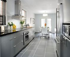 White shaker kitchen cabinets grey floor grey cabinets with black counters wood floors color appliance house Black And Grey Kitchen, Kitchen Cabinets Grey And White, Grey Kitchen Floor, Modern Grey Kitchen, Light Gray Cabinets, Light Grey Kitchens, Grey Kitchen Designs, Kitchen Flooring, Gray Floor