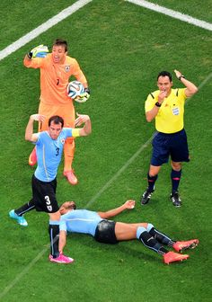 Referee Carlos Velasco Carballo signals for a trainer for Alvaro Pereira of Uruguay after a collision as teammates Diego Godin (L) and Ferna...