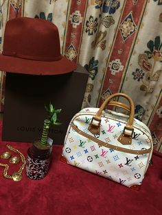 AuthenticLouis Vuitton White Monogram Multicolore Trouville Bag serial # MI0095 is the smaller version of the famous Deauville vanity case and makes the perfect city bag. With its vibrant colors, golden studs, this sleek structured bag will hold all your daily essentials in style.  Selling for $800