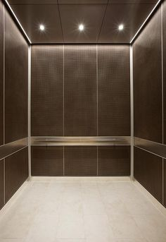 Elevator Interior in Bonded Bronze with Dark Patina and Charleston pattern; handrail panels in Stainless Steel with Seastone finish; Satin Stainless Steel Rectangular handrail at Baylor Charles A. Lift Design, Cabin Design, Wall Design, Lobby Interior, Office Interior Design, Apartment Interior, Hotel Interiors, Office Interiors, Garage Lift